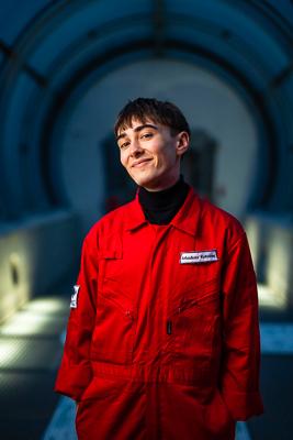 portret Arka Kołodzieja w czerwonym kombinezonie astronauty, młody lekarz uśmiecha się szeroko i trzyma ręce w kieszeni