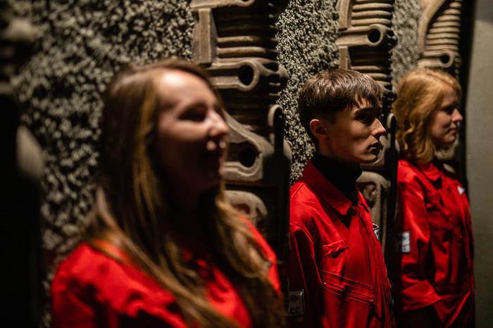 trójka członków zespołu Innspace stoi pod ścianą w mrocznym oświetleniu
