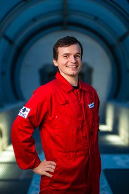 portret Huberta Gross w czerwonym kombinezonie astronauty, kontruktor stoi bokiem i uśmiecha się szeroko do zdjęcia