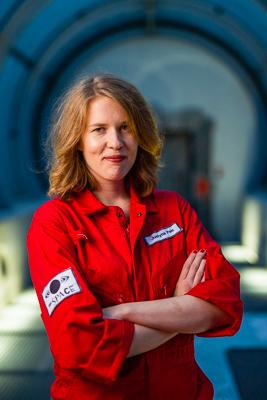 portret Justyny Pelc w czerwonym kombinezonie astronauty, liderka zespołu zakłada ręce jedna na drugą i uśmiecha się