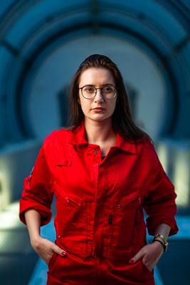 portret Katarzyny Gawlik w czerwonym kombinezonie astronauty, optometrystka trzyma ręce w kieszeni