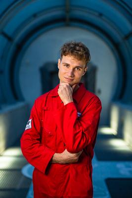 portret Łukasza Sokołowskiego w czerwonym kombinezonie astronauty, grafik Innspace podpiera brodę na ręce