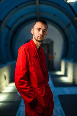 portret Marcina Zielińskiego, fotografa Innspace, w czerwonym kombinezonie astronauty