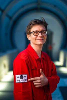 portret Piotra Torchały w czerwonym kombinezonie astronauty, Piotr wskazuje palcem na logo Innspace naszyte na ramieniu