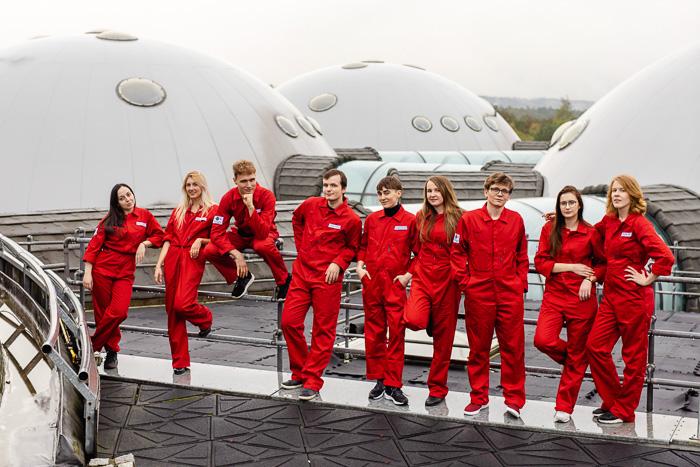 członkowie zespołu innspace pozują do zdjęcia grupowego w czerwonych kombinezonach na terenie Alvernia Studios